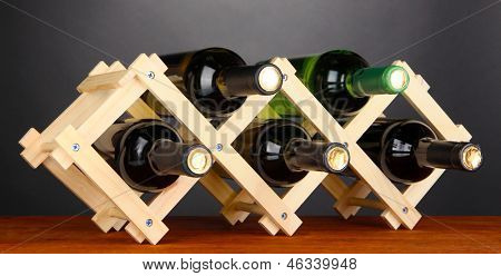 Bottles of wine placed on wooden stand on grey background