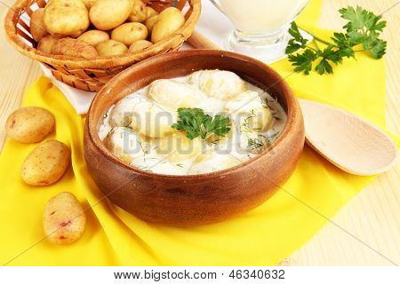 Concursos jovens batatas com creme de leite e ervas em tigela de madeira em close-up de toalha de mesa