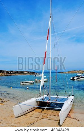 a sailboat and the Mediterranean Sea in Cala Sa Roqueta cove, in Formentera, Balearic Islands, Spain, and the typical slipways and fishermen huts, called barraques