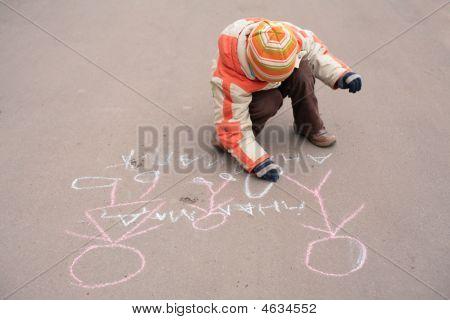 Boy Sketches By Chalk On Asphalt