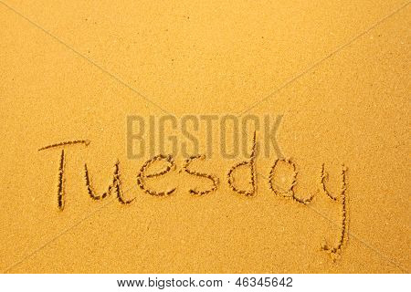 Tuesday - written in sand on beach texture.