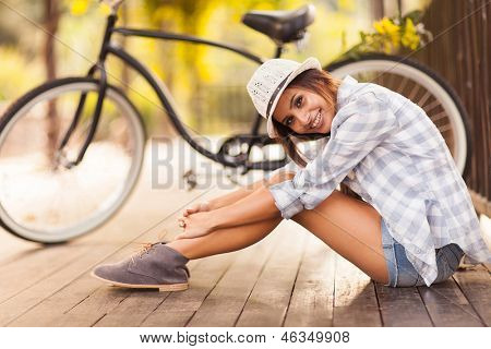 beautiful young woman sitting next to her bike outdoors