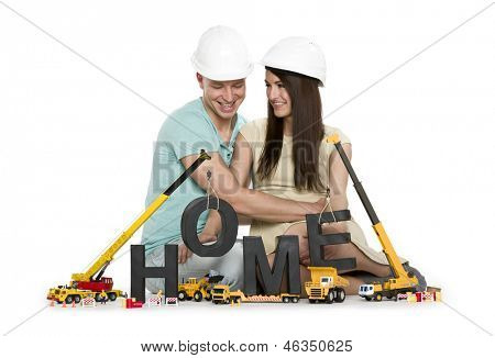 Building up home concept: Happy young man and woman along with construction machines building the word home, isolated on white background.
