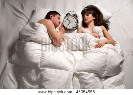 Quiet  young couple sleeping together and ignoring alarm clock bell