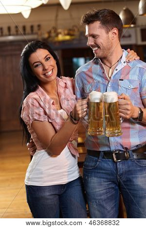 Happy young couple drinking beer in pub, clinking glasses, smiling.