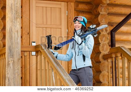 Female downhill skier hands skis and poles standing near wooden door of the house