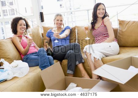 Three Girl Friends Relaxing With Champagne By Boxes In New Home Smiling