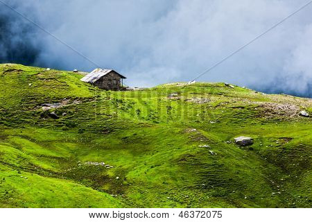 Serenity serene lonely scenery background concept - house in hills in mountins on alpine meadow in clouds
