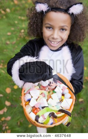 Young Girl Outdoors In Cat Costume On Halloween Holding Candy