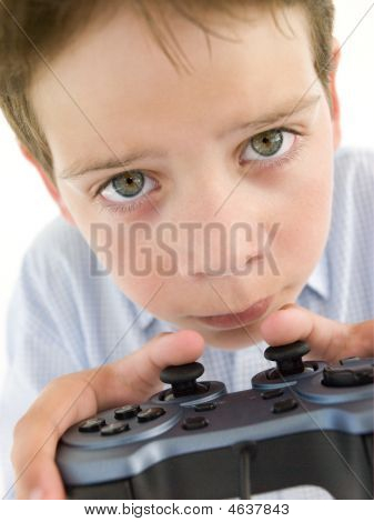 poster of Young Boy Using Videogame Controller And Concentrating