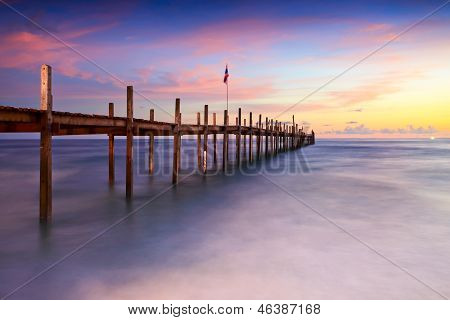 Bridge on beach in sunset and sea wave