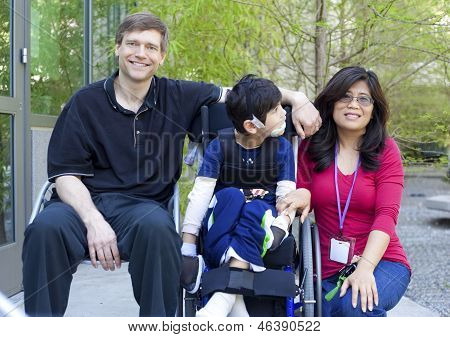 Disabled Child In Wheelchair With His Parents