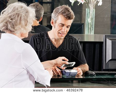 Hairdresser with female client paying with mobilephone over electronic reader at counter