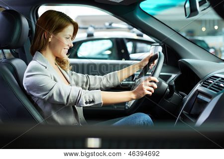 Photo of young woman choosing a new car in automobile center