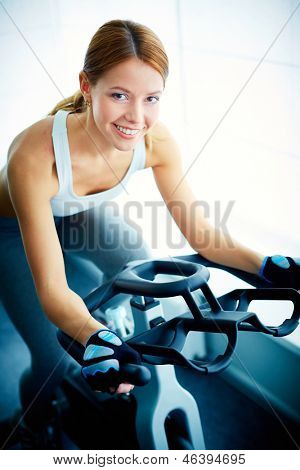 Portrait of young female looking at camera while training on simulator in gym