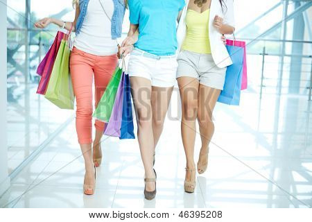 Legs of three glamorous girlfriends with paperbags walking down trade center