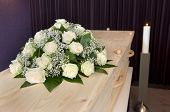 stock photo of mortuary  - A flower arrangement on a coffin and a burning candle on the background in a mortuary - JPG