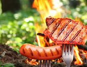 foto of bonfire  - Sausage and steak on a fork - JPG