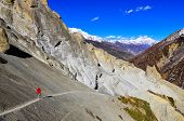 stock photo of sherpa  - Trekker in red jacket walking in Himalayas mountains Nepal - JPG