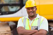 stock photo of mine  - smiling african mine worker with arms folded at mining site - JPG