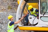 stock photo of ppe  - happy construction manager handshaking with bulldozer operator at construction site - JPG