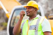 afro american industrial worker talking on walkie-talkie at mining site