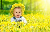 stock photo of meadows  - Beautiful happy little baby girl in a wreath on a meadow with yellow flowers dandelions on the nature in the park - JPG