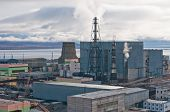 image of chukotka  - Smoking pipes of thermal power plant against cloudy sky in Anadyr town Chukotka Republic of Russia - JPG
