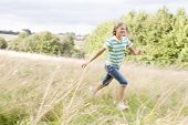 Young Girl Running In A Field Smiling