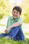 Young Boy Sitting Outdoors Smiling