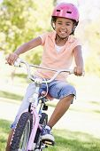stock photo of young girls  - Young girl on bicycle outdoors smiling - JPG