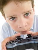 Young Boy Using Videogame Controller And Concentrating poster