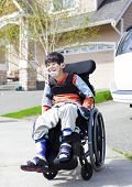 foto of biracial  - Happy disabled six year old boy waiting on sidewalk in wheelchair - JPG
