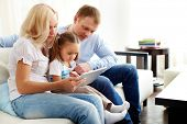 Portrait of happy parents with their daughter sitting on sofa with digital tablet