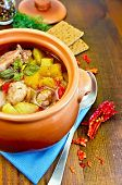 foto of pot roast  - Roast with chicken meat potatoes and peppers in a clay pot napkin spoon crispbreads dill on a wooden board - JPG