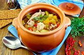 image of pot roast  - Roast with chicken meat potatoes and red pepper in a clay pot blue napkin spoon crispbreads dill and pepper in a jar on the board - JPG