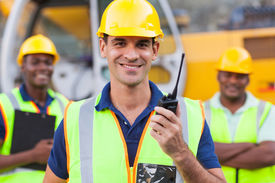 stock photo of ppe  - portrait of smiling contractor with walkie - JPG