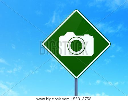 Travel concept: Photo Camera on road sign background