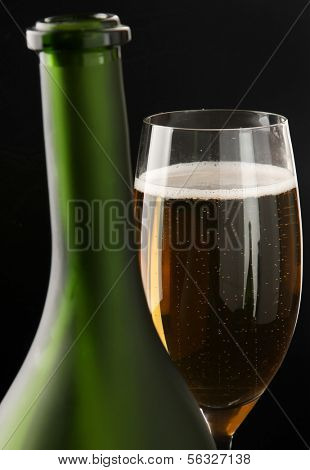 A glass of champagne near a bottle, focus on the glass