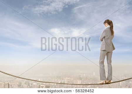 Chinese business woman stand on rope. Photo manipulation about risk, adventure, future or dream etc.