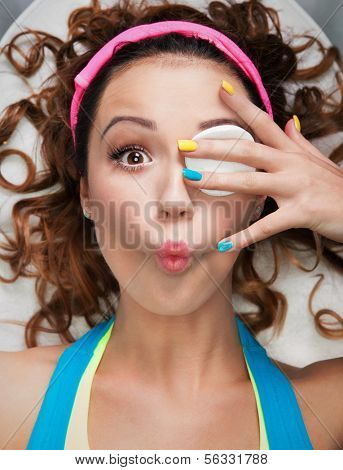 Make up removal concept, woman with cotton pad making funny face