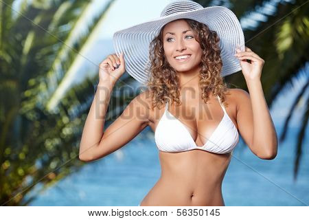 Happy young woman posing in straw hat at exotic surrounding