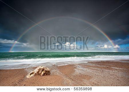 Rainbow Over Stone Beach In Atlantic Ocean