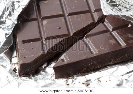 Broken bar of pure brown chocolate lying on tinfoil