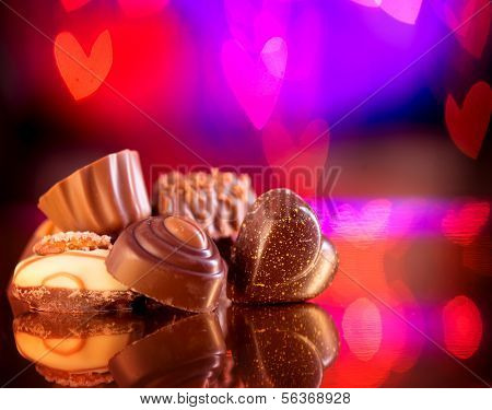 Valentine Chocolates. Assorted Chocolate Candies. Chocolate Sweets. Candy Border Design over Purple Hearts Bokeh Background. Heart Shaped Chocolate