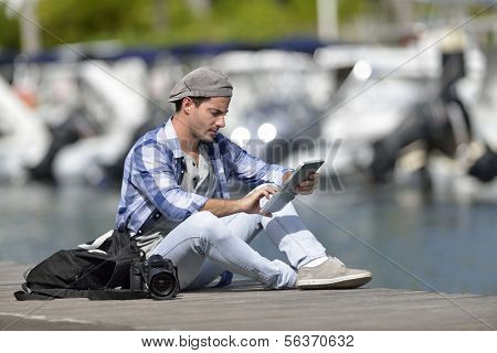 Adventurer looking at photo shots on tablet