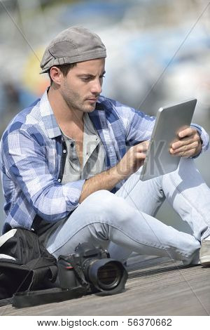 Globe-trotter using digital tablet during journey