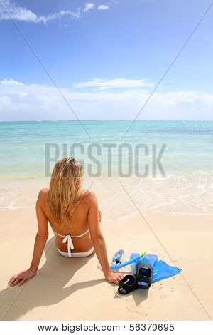 Rear view of woman relaxing on the beach