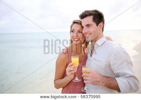 Couple enjoying cocktail on caribbean beach