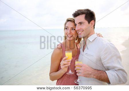 Couple enjoying cocktail on caribbean beach